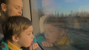 Small boy with mother sitting against window in their rail train place and watching outside stock footage