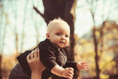 Small boy in mothers hands on natural background. Child with blond hair outdoor. Mothers son enjoy idyllic day. Childhood trust and love concept stock image