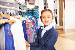 Small boy in navy suit standing near clothes Stock Images