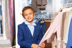 Small boy near clothes holding sweater's arm Stock Images