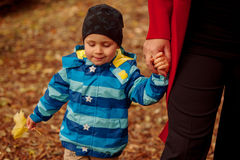 Small Boy near his Mother. Small boy walking in the park close to his mother Royalty Free Stock Photography