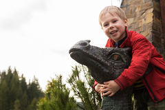 Small boy near a stone sculpture of a dragon Stock Images