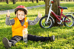 Small boy out riding giving a thumbs up. Small boy out riding his bicycle in the park giving a thumbs up of approval as he sits in his safety gear on green grass Royalty Free Stock Photos