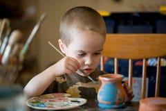 Small boy pains the clay jar Royalty Free Stock Photos