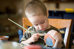 Small boy pains the clay jar. By brush Royalty Free Stock Photography