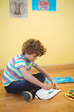 Small boy painting on some paper. On the floor Royalty Free Stock Image