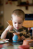 Small boy paints the clay pot Royalty Free Stock Photo