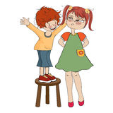 Small boy perched on a chair with funny girl Stock Image