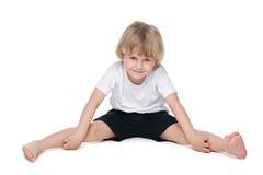 Small boy performs gymnastic exercises Stock Photos