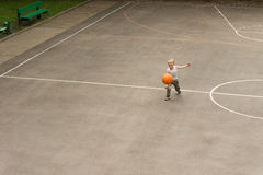 Small boy playing basketball bouncing the ball Stock Photos