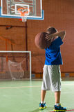 Small boy playing basketball. Preparing to throw the ball as he stands with his back to the camera on an indoor court Stock Photo