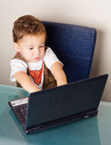 Small boy playing with a computer Royalty Free Stock Images
