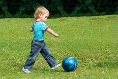 Small boy playing football in park outdoor. Small boy playing football in the park outdoor. Two years child running forward Stock Photos