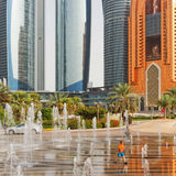 Small Boy Playing in Fountains in front of Abu Dhabi's Corniche High Rises Stock Images
