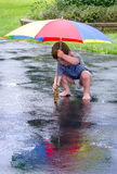 Small boy playing in the rain royalty free stock photos