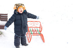 Small boy playing with a sled in snow Stock Images