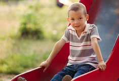Small boy playing on a slide in a kids playground stock image
