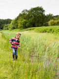 Small boy playing with a stick in nature Stock Photography
