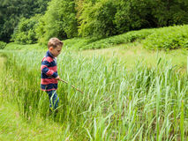 Small boy playing with a stick in nature Royalty Free Stock Images