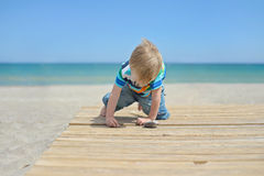 Small boy playing with stones on the beach Stock Photography