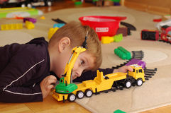 Small boy playing with toy truck. On the floor in his room Stock Photos