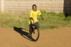 Small Boy Playing with Tyre. Young african child, wearing a bright yellow T-shirt, playing with the tyre of a 24 inch bicycle, in front of a raw concrete brick Royalty Free Stock Photos