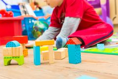 Small boy playing with wooden blocks Stock Image