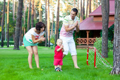 Small boy plays football with parents Royalty Free Stock Image