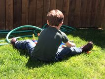 Small boy plays in Lawn Stock Photos