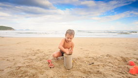 Small Boy Plays with Wet Sand Fills Bucket on Sea Beach stock video footage