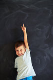 Small boy pointing upwards with forefinger of stretched arm agai Stock Photos