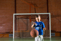 Small boy practicing bouncing a basketball Stock Images