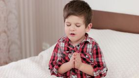 Small boy praying, kid saying prayer before going to bed, strong belief in heart, boy praying to god