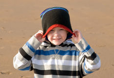 Small boy pulling hat over his head Stock Photo
