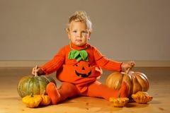 Small boy in pumpkin costume posing at studio.  stock image