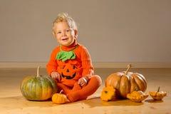 Small boy in pumpkin costume posing at studio.  stock photos