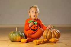 Small boy in pumpkin costume posing at studio.  stock photography