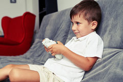 Small boy is rapt in playing a videogame sitting on grey sofa Stock Photo