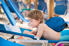 Small boy reading a book on a deck chair Stock Image