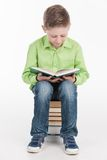 Small boy reading book on white background. Stock Image