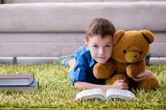 The small boy reading books at home stock photography