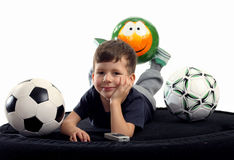 Small boy recreation on sofa with three balls Stock Images