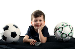 Small boy recreation on sofa with two balls Royalty Free Stock Images