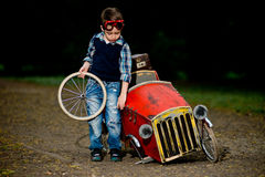 Small boy repair red car. In park Stock Image