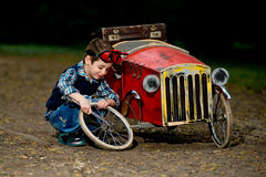Small boy repair red car. In park Stock Photos