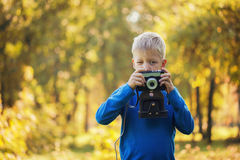 Small boy with retro camera photographing outdoors at sunny autu Stock Images