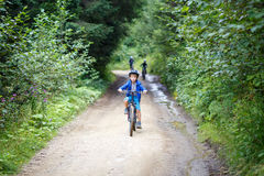 Small boy riding the bicycle on mountain road Royalty Free Stock Photo