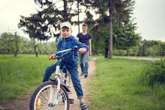 Small boy riding a bike together with his father Stock Photos