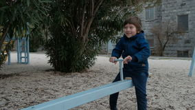 Small boy riding seesaw in playground in winter. Nobody else. Toddler with dark hair in sneakers, blue trousers, plaid coat without cap, gloves sit on wooden stock footage