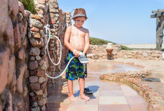 Small boy rinsing off the sand from his shoes. After spending day beach tropical resort using  special wall mounted hose pip outdoors Stock Images